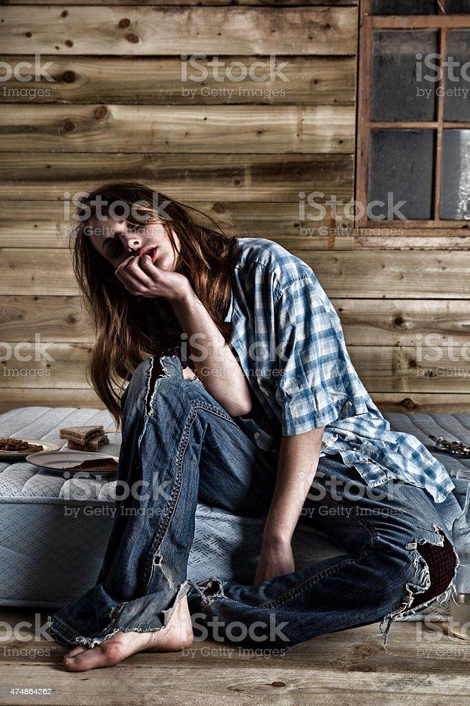 Junkie Sitting On A Dirty Mattress stock photo