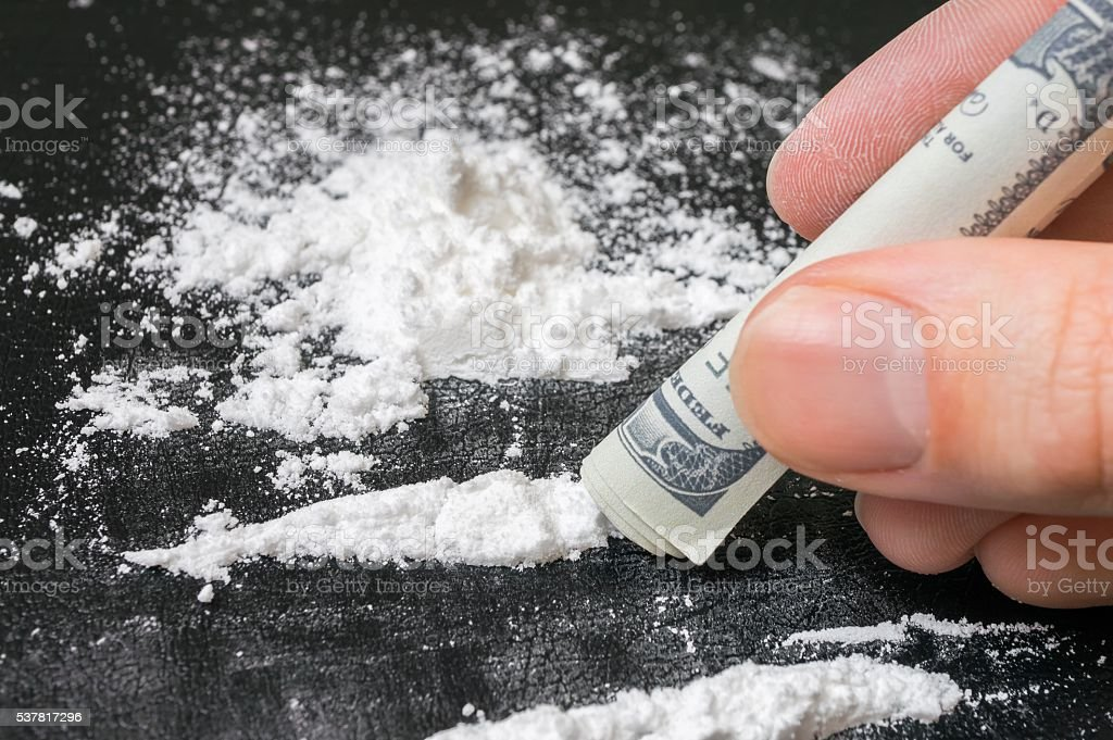 Junkie snorting cocaine white powder with rolled banknote. Narcotics concept. stock photo