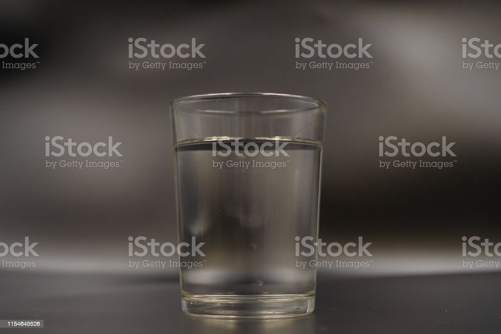 Just a glass of water on a dark wooden table. Mineral water in a...