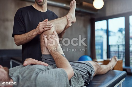 Shot of a young man visiting his physiotherapist for a rehabilitation session