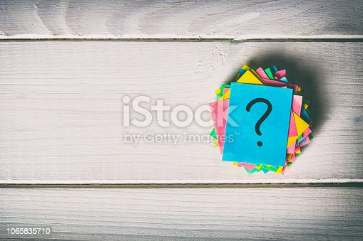 istock Just a lot of question marks on colored papers. vintage background 1065835710