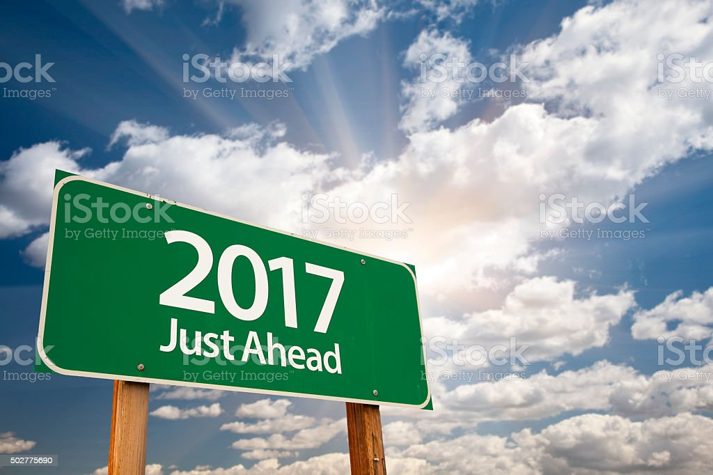 2017 Just Ahead Green Road Sign Against Clouds stock photo