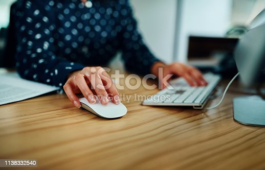 Closeup shot of an unrecognizable businesswoman working on a computer in an office at night