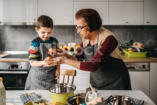 Grand mother and her grand son, mixing eggs for cake