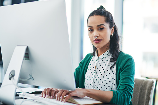Portrait of a young businesswoman using a computer in a modern office