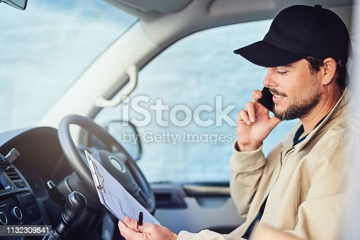 Shot of a courier talking on a cellphone while sitting in a delivery van