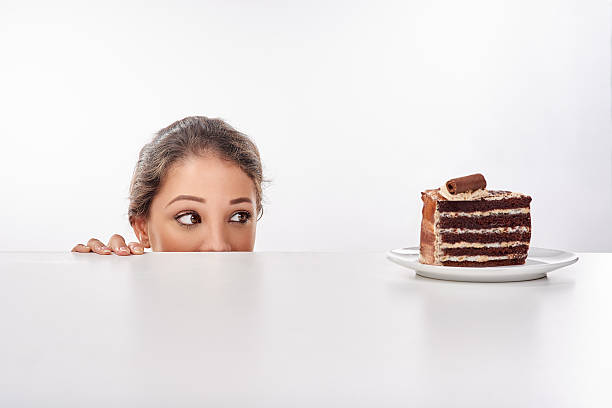 I just can't look away... Shot of a young woman sneak up to a piece of cke standing on a table temptation stock pictures, royalty-free photos & images