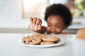 Cropped shot of an adorable little girl stealing cookies at home