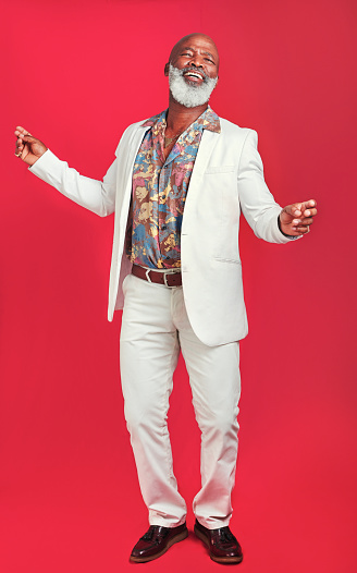 Studio shot of a man wearing vintage clothes while dancing against a red background