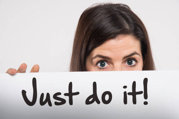 just do it motivation young woman young woman holding a whiteboard written just do it on it motivation taking the plunge stock pictures, royalty-free photos & images