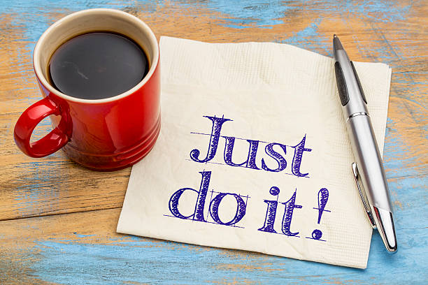 Just do it motivational advice Just do it motivational advice on napkin with a cup of coffee. Motivation concept. taking the plunge stock pictures, royalty-free photos & images
