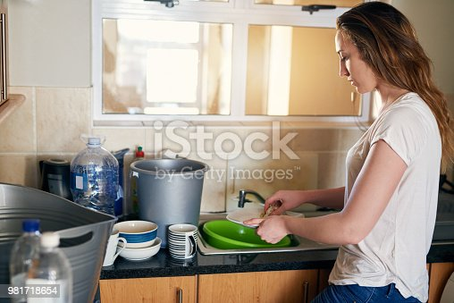 Cropped shot of a beautiful young woman doing dishes and trying to save water in the kitchen at home