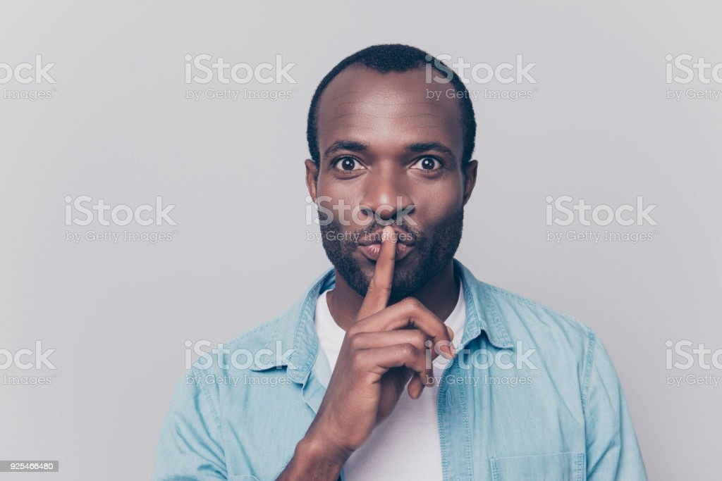 Just don't speak! Close up portrait of handsome cheerful mysterious silent man making hush gesture, isolated on gray background stock photo