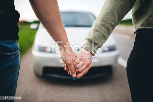 Young caucasian couple holding hands outdoors infront of their car. Engagement ring on womans finger,