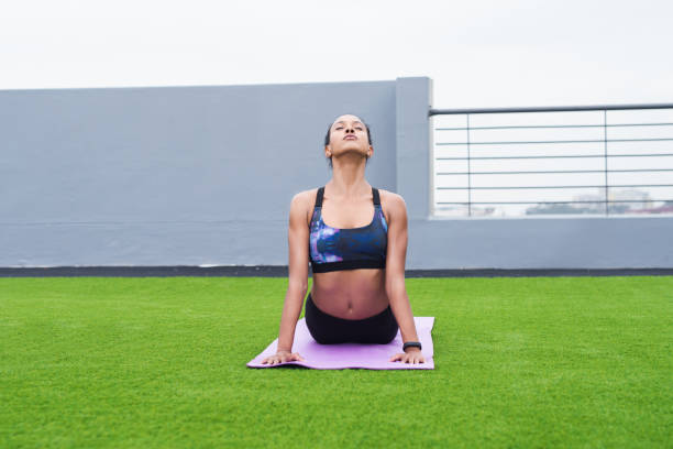 Just focus on all the calm Shot of a sporty young woman practising yoga outdoors upward facing dog position stock pictures, royalty-free photos & images