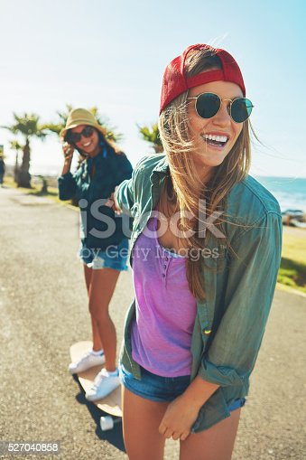 Shot of two friends hanging out on the boardwalk with a skateboard