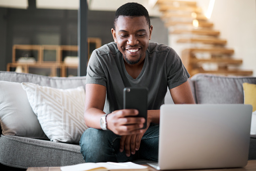 Shot of a young man using a cellphone and laptop at home