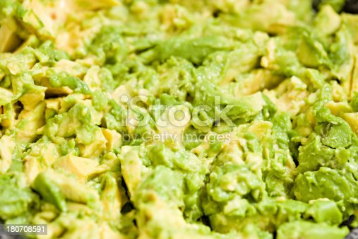 A high angle extreme close up shot of smashed avocado in a bowl.