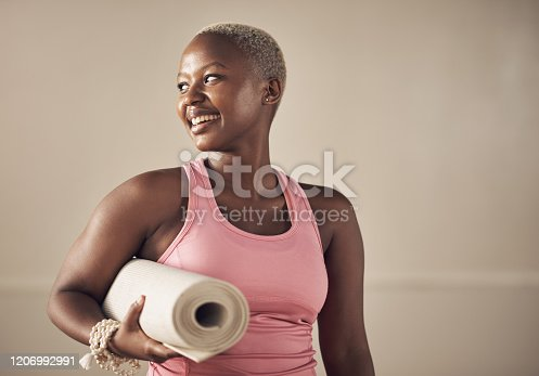 Cropped shot of an attractive young woman standing alone and holding her yoga mat before an indoor yoga session