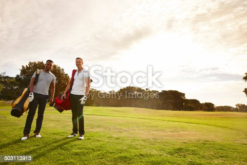 Portrait of two young men standing on a golf course