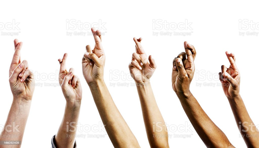 Six mixed hands are raised, all with fingers crossed superstitiously,...