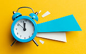Alarm clock and colour papers on the yellow background.