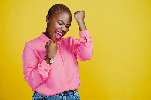 Cropped shot of an attractive young woman celebrating and feeling cheerful against a yellow background