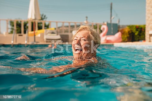 Senior woman swimming in a swimming pool while on holiday in Paphos, Cyprus. She is looking at the camera and smiling as she swims.