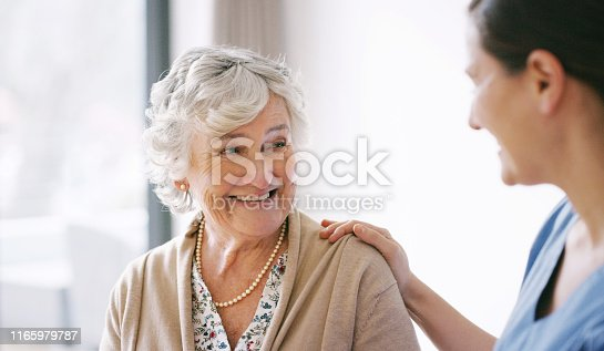 Shot of a happy senior woman being cared for by a young nurse in a retirement home