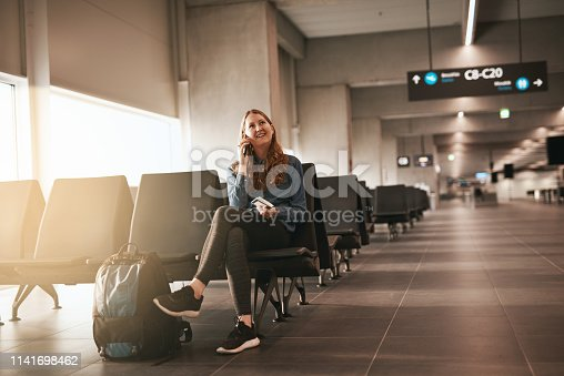 Shot of a young woman using her cellphone while sitting in the airport lounge area