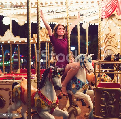 Beautiful caucasian girl at the carousel.