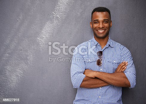 A handsome young man leaning against a blue/gray wall