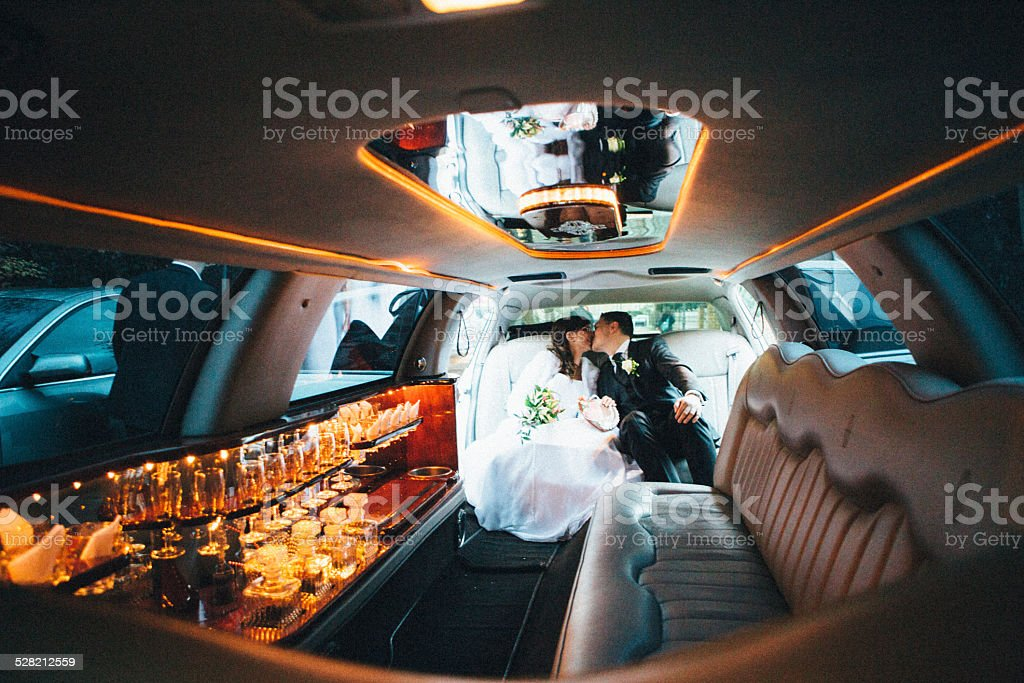 just married: Bride and groom sitting in a stretch limousine stock photo