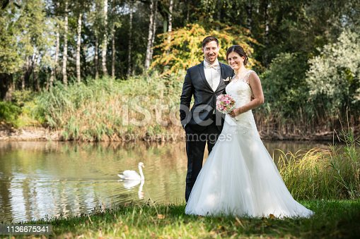Just married bride and groom looking happy at the camera. They are standing side by side at an idyllic place at a lake, a swan is swimming in the background.