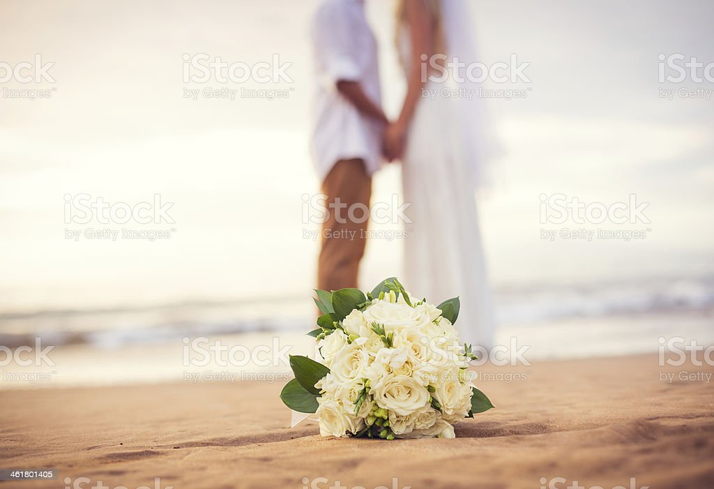 Just married couple holding hands on the beach stock photo