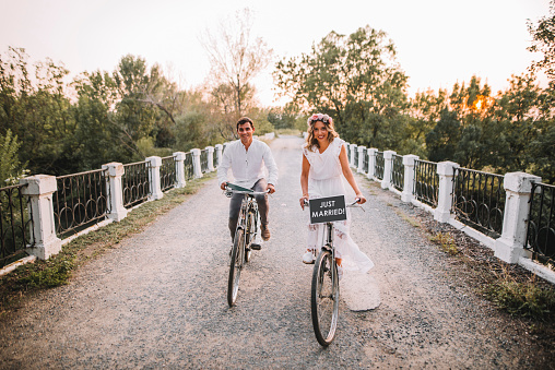 A just married couple riding their bikes after getting married.