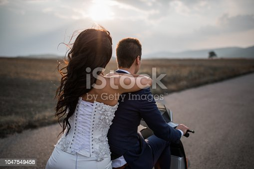 Just married couple on the vespa motorbike going on the honeymoon