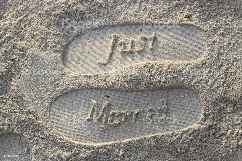Just married footprints pressed into sand at the beach stock photo