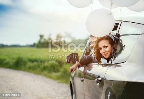 Couple just married celebrate their love, driving in car