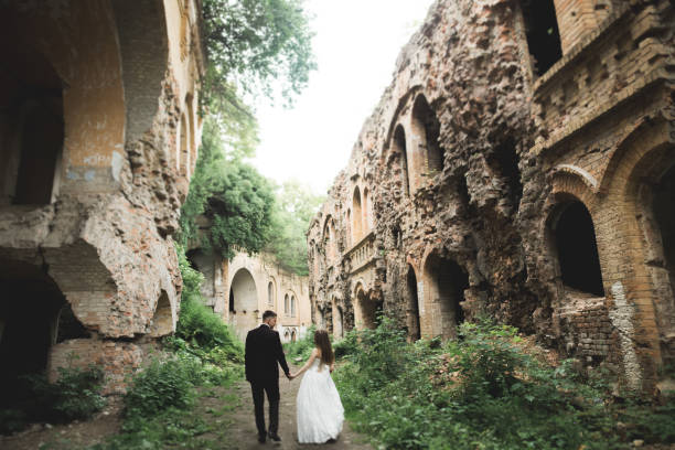 Just married poses and kissing with an old fortress on the background stock photo