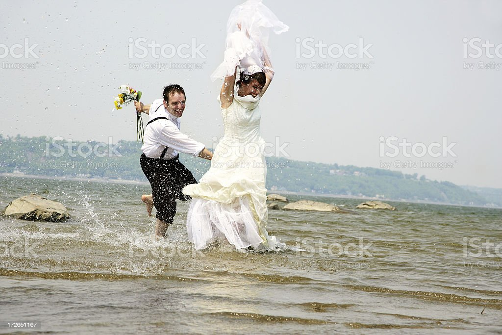 Just married running in water VI royalty-free stock photo