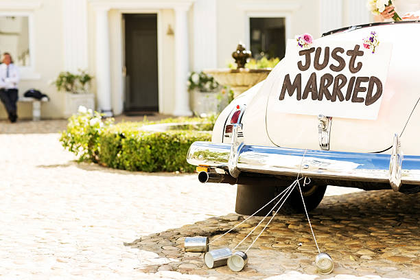 just married sign and cans attached to car - pas getrouwd stockfoto's en -beelden