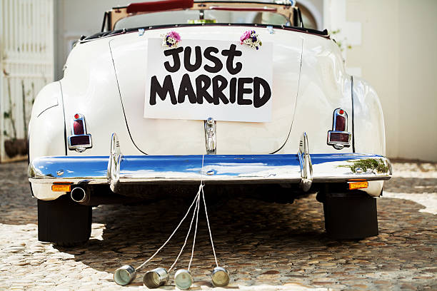 just married sign and cans attached to car's trunk - pas getrouwd stockfoto's en -beelden