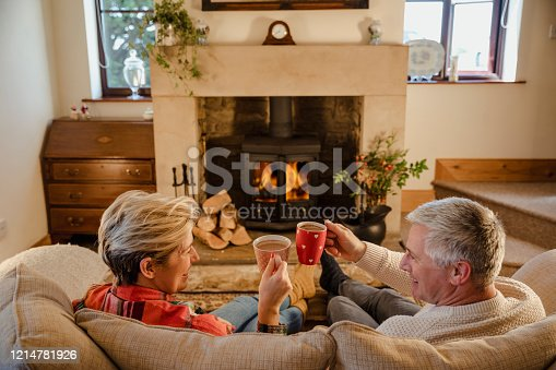 Mature caucation couple sat infront of a fire drinking hot chocalate from mugs.
