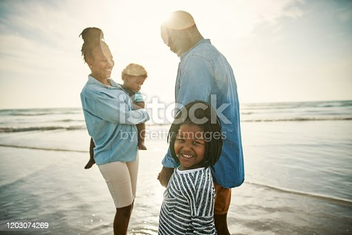 Shot of a young family spending time together at the beach