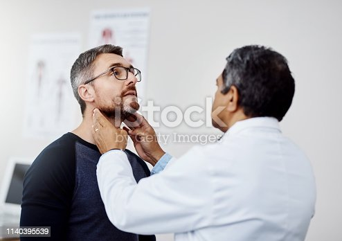 Shot of a confident mature male doctor doing a checkup on a patient inside of a hospital during the day