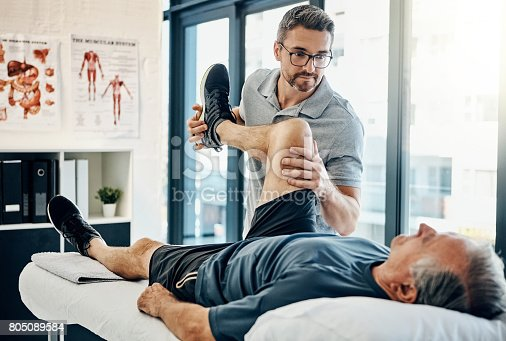 Shot of a friendly physiotherapist treating his mature patient in a rehabilitation center