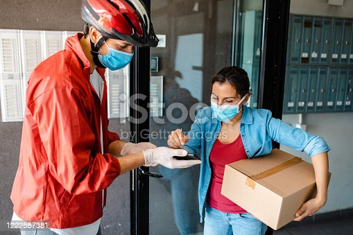 Delivery person deliver a package to a customer, and she signing a delivery parcel on digital device while both wearing protective gloves and face masks during corona virus pandemic