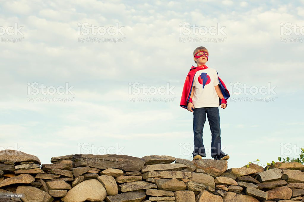 A young boy dressed as a superhero is standing tall against adversity.