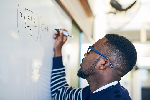 Cropped shot of a young man writing on a whiteboard in a classroom